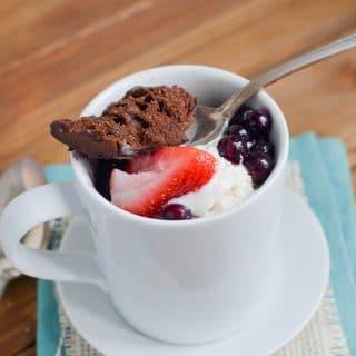Paleo chocolate mug cake with berries and ice cream in mug.