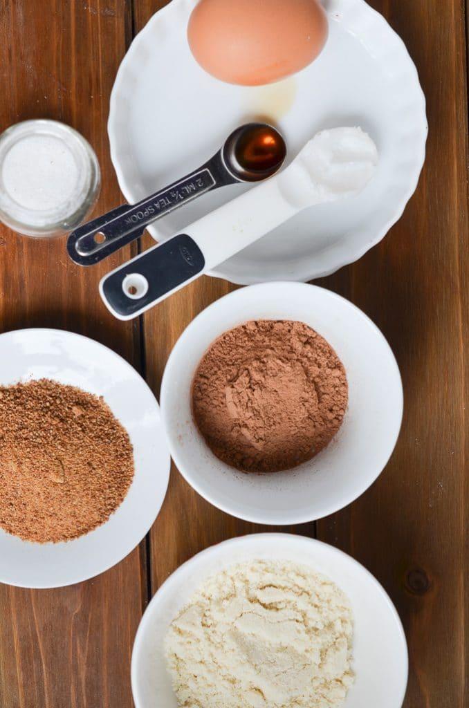 Paleo chocolate mug cake ingredients in bowls on counter.