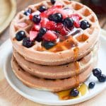 Paleo waffles on a plate with berries and maple syrup.
