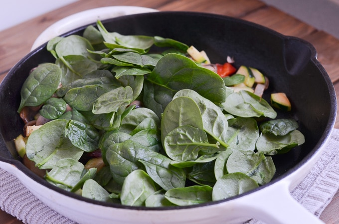 spinach is added to sauteing veggies in cast iron skillet.