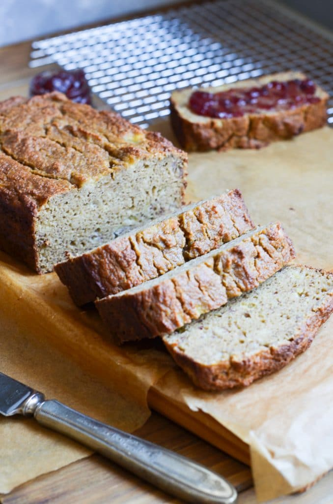 Banana bread with slices on chopping block.