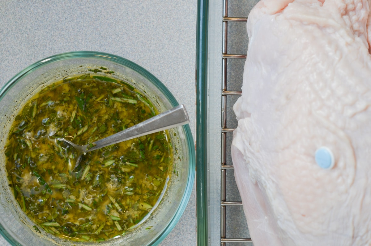 herb seasoning mix in bowl and uncooked turkey breast in roasting pan.