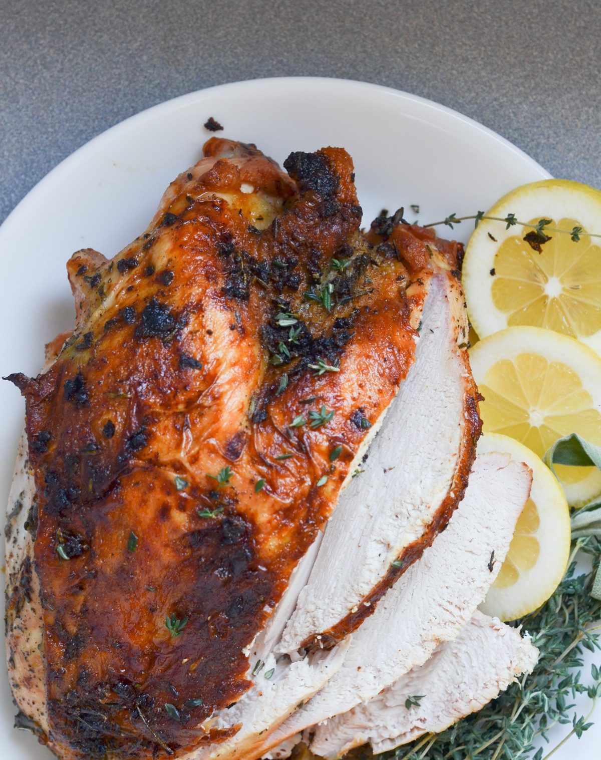 Roasted turkey breast on platter with lemons, thyme bunches.